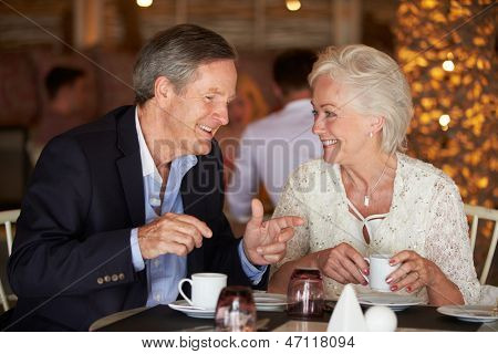 Senior Couple Enjoying Cup Of Coffee In Restaurant