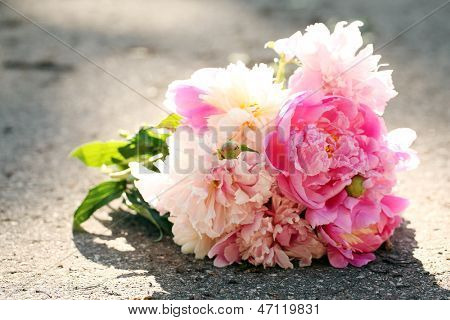 Bouquet of beautiful rose peonies left on a road