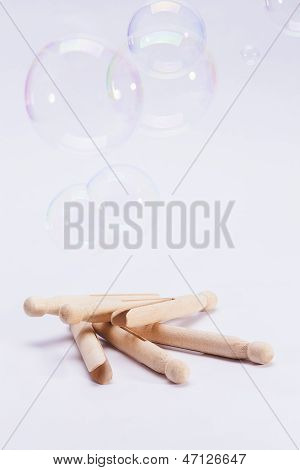 Wooden Dolly Clothes Pegs And Bubbles On White Background
