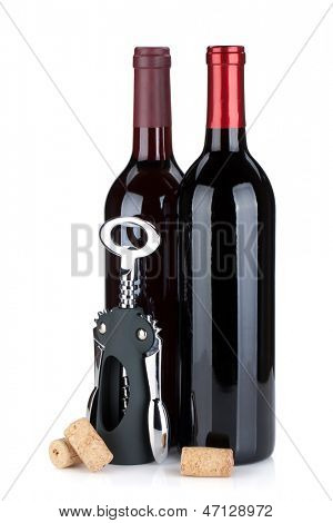 Two red wine bottles, corks and corkscrew. Isolated on white background