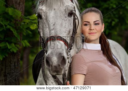 portrait of a pretty young woman with a white horse (Focus on horse)