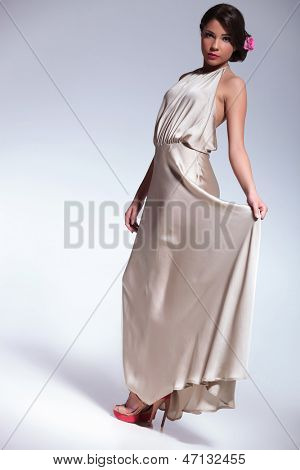 full length photo of a young beauty woman holding her dress with a hand and looking with innocence at the camera. on gray background