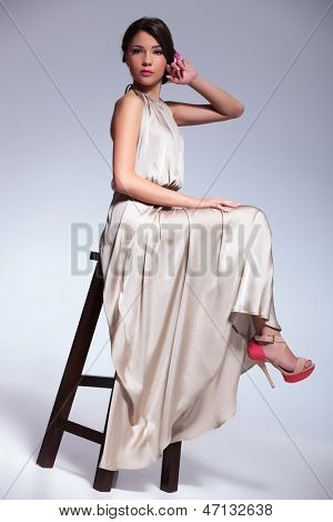 young beauty woman posing on a high chair with her hand at her face and her legs suspended in the air. on gray background