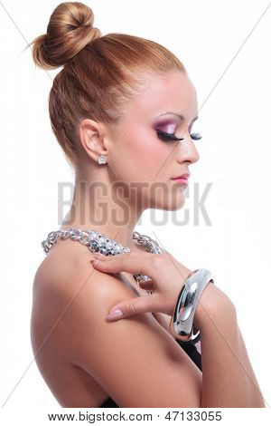side view closeup of a young beauty woman looking down while holding her hand on her shoulder. on background