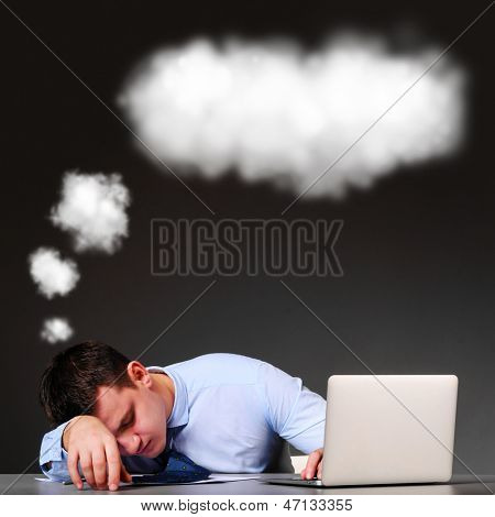tired businessman is sleeping at his table with laptop and a cloud above his head
