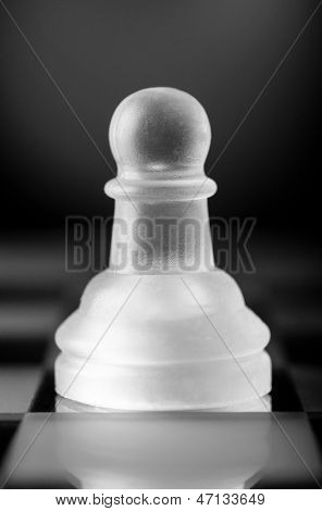 glass chess pawn is standing on board in dark