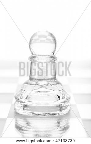 glass chess pawn is standing on board, cut out from white background