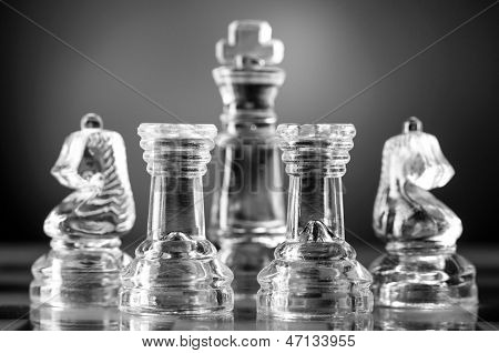 glass chess pieces are defending the king on board in dark