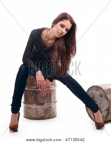 Girl In Jeans Sitting On An Iron Barrel