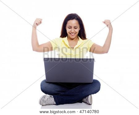 Young beuatiful woman celebrating while using her laptop on a white background