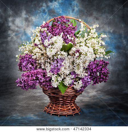 Still life, a beautiful lilac and lily of the valley in the bask