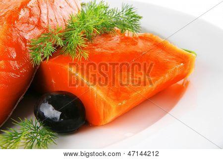sinlge pink salmon bit on a big white dish