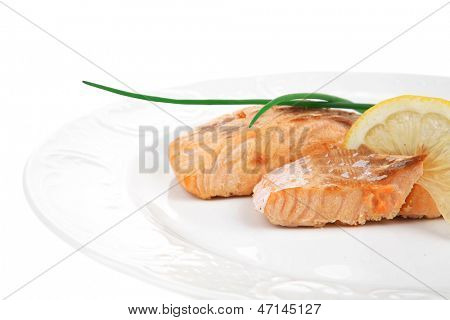 savory fish portion : grilled norwegian salmon fillet with green chinese onion, and lemon slice on white plate isolated over white background