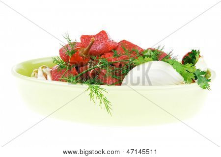 fresh uncooked beef meat slices over ceramic bowls ready to prepare with red peppers and greenery isolated over white background