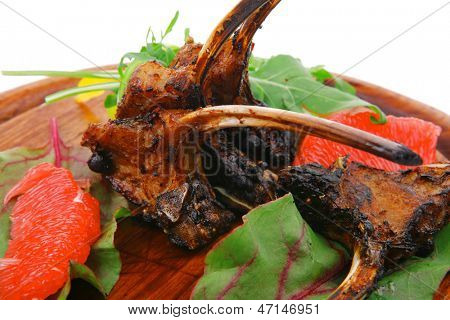 main portion : grilled ribs on wooden plate isolated over white background with salad leaves and red grapefruit