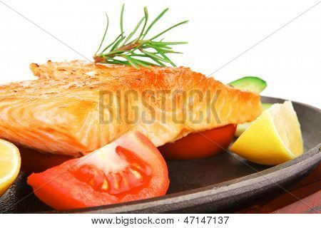 food: roast salmon on metal pan over red wooden plate isolated over white background