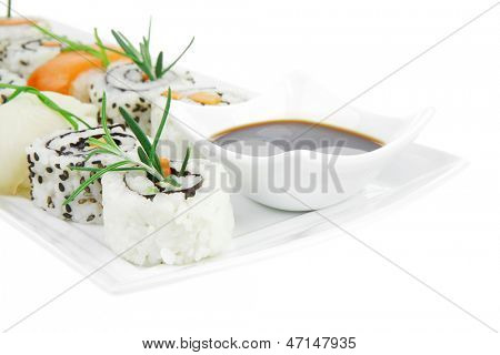 California Roll with Avocado and Salmon, Cream Cheese and Raw Salmon inside. on long white plate . isolated over white background . Maki Sushi and Sashimi