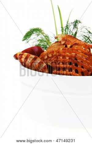 potato chips served with small pickled eggplants in small white bowl isolated on white background