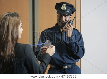 Security guard checking businesswoman's credentials