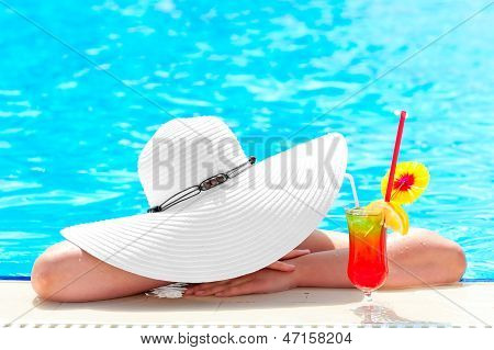 girl in the pool with a cocktail