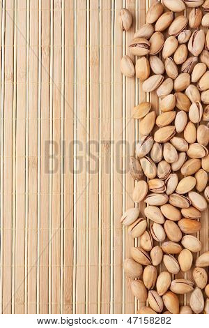 Unpeeled Pistachios Lying On A Bamboo Mat