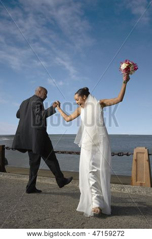 Newlyweds dancing on a pier
