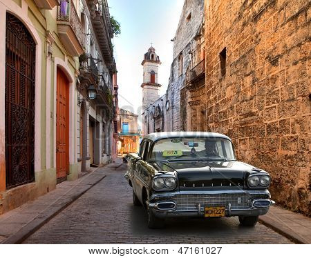 HAVANA, CUBA-MAY 14: Street scene with an old rusty american car on May 14, 2013 in Havana.These classic vintage cars that can be seen all over the country have become a worldwide known symbol of Cuba