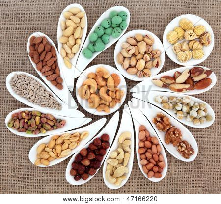 Nut selection in white porcelain bowls over hessian background.