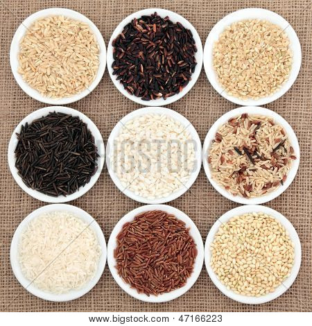 Rice grain varieties in white round porcelain bowls over hessian background.