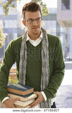 Outdoor portrait of male student holding books outdoors.