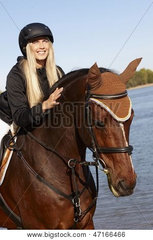 Closeup photo of young female rider leaning over horse at riverside.
