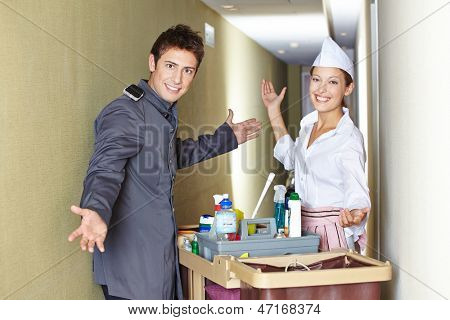 Concierge and hotel maid with cleaning cart in corridor