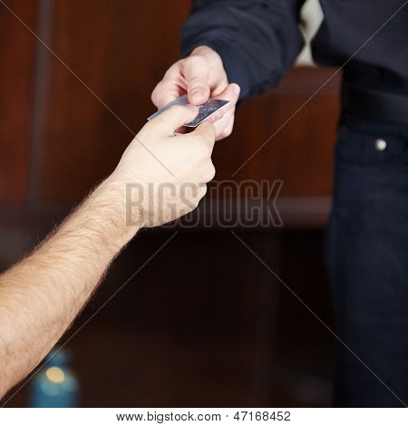 Hand giving credit card to waiter for payment in a restaurant