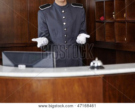 Concierge with empty white gloves behind hotel reception counter