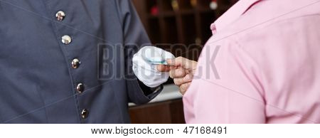 Hand of a concierge giving hotel room card to woman