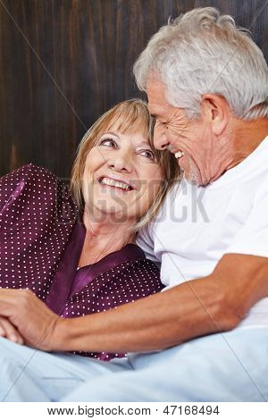 Happy senior couple having fun in bed in a hotel room