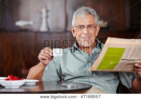 Happy senior man sitting with coffee and newspaper in a caf���©