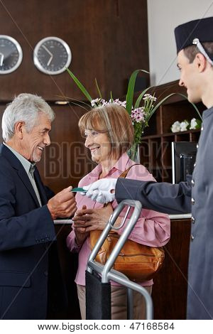Senior couple getting key card in hotel from concierge