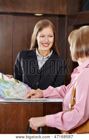 Happy female receptionist in hotel offering city map to senior guest