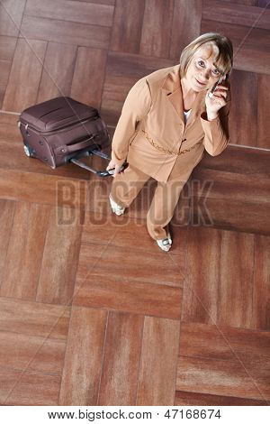 Senior woman pulling her suitcase and making phone call with her smartphone