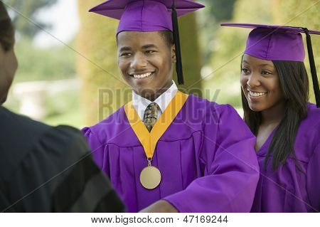 Closeup of a graduate looking at cropped dean with female friend