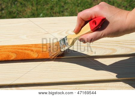 Man painting wooden furniture piece