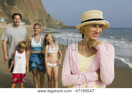 Smiling grandmother with blurred family in the background at beach