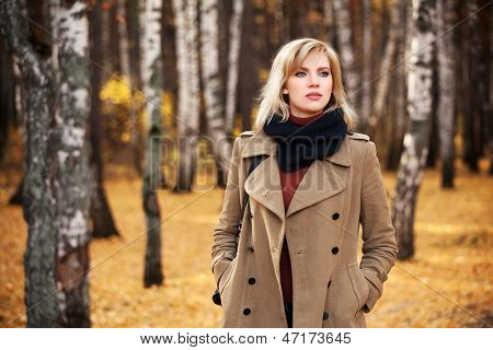 Blond woman walking in autumn forest