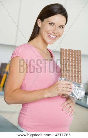 Pregnant Woman In Kitchen With Large Chocolate Bar Smiling