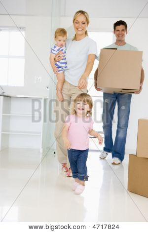 Family With Box Moving Into New Home Smiling