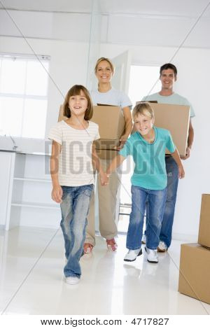 Family With Boxes Moving Into New Home Smiling