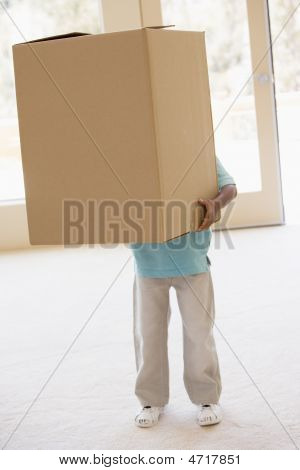 Young Boy Holding Box In New Home