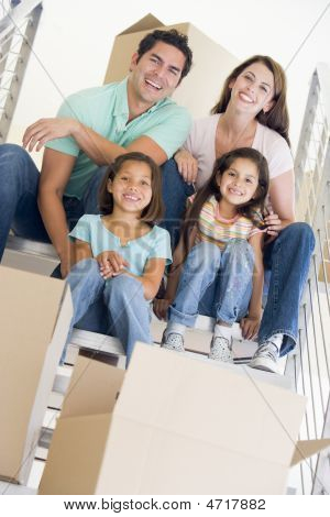 Family Sitting On Staircase With Boxes In New Home Smiling