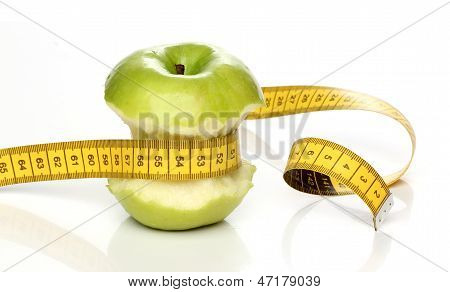 Eaten green apple and a measuring tape isolated